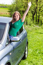 Happy young woman waving out the window of her new car Stock Photos