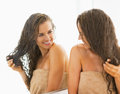 Happy young woman with wet hair looking in mirror bathroom Royalty Free Stock Images