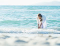 Happy young woman wetting hands in sea high resolution photo Royalty Free Stock Images