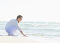 Happy young woman wetting hands in sea white dress Stock Photos