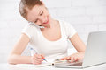 Happy young woman working at a laptop at home with your phone Royalty Free Stock Photo