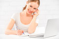 Happy young woman working at a laptop at home with your phone Royalty Free Stock Image