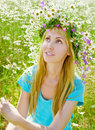 The happy young woman in a wreath from wild flower Royalty Free Stock Image
