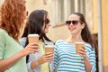 Happy young women drinking coffee on city street Royalty Free Stock Photo