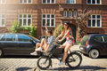 Happy young women riding on a bicycle Royalty Free Stock Photo