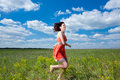 Happy young women running on summer field Royalty Free Stock Photo