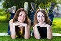 Happy young women smiling lying on grass against background of summer green park Stock Images