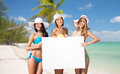 Happy young women with white board on summer beach Royalty Free Stock Photo
