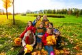 Hapy kids in the park group of happy sit on grass holding bouquets of autumn maple leaves and smiling Stock Photo