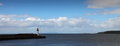 Harbor lighthouse panoramic view of at mouth with blue sky and cloudscape background Stock Images