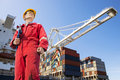 Harbor master with clipboard overalls hard hat and safety glasses standing in front of a large container ship being unloaded Royalty Free Stock Image