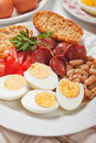Hard boiled eggs hardboiled chicken with beans and sausage served for breakfast Stock Photos