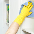 Hard to reach gloved hand cleaning a bookshelf with a microfibre cloth Royalty Free Stock Image