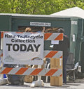 Hard to recycle day asheville north carolina usa april people stuff a dumpster with cardboard items behind a sign saying hardpto Royalty Free Stock Photo