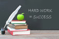 Hard work equals success is written on a blackboard with a pile of books quill and ink Royalty Free Stock Photography