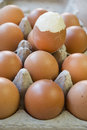 Hardboiled egg partly shelled on a series of raw eggs Stock Photo