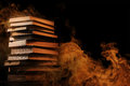 Hardcover books with swirling smoke pile of surrounded tendrils or vapor in a darkened vintage style room conceptual of magic fire Stock Photos