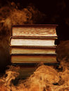 Hardcover books with swirling smoke pile of surrounded tendrils or vapor in a darkened vintage style room conceptual of magic fire Stock Photo