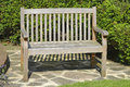 Hardwood garden seat placed in a sunny corner of a domestic Royalty Free Stock Images