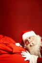 Hark portrait of santa claus leaning over huge red sack Stock Image