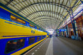 Harlem, Amsterdam, Netherlands - July 14, 2015: Inside railroad station, large roof covering platform, blue and yellow Royalty Free Stock Photo