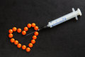 Harm of drug addiction. Heart made of red tablets and syringe