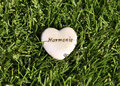 Harmony heart in grass white green image taken outside as a closeup sign for calm and love Stock Photo