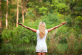 Harmony with nature back woman raised hands in the forest Stock Image