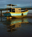 Harmony wooden fishing boat landscape of colorful view reflect shadow on water tide going out let black sand and hold of Royalty Free Stock Photography