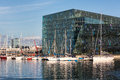 Harpa concert hall with sailboats reykjavik iceland the in on a sunny day harbor and in foreground and the city in the background Royalty Free Stock Image