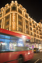 Harrods department store. Red bus passes in front of the building