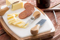 Harvati cheese with sliced spicy sausage served on a cheeseboard cutters alongside a bottle of red wine a Stock Photography