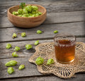 Harvest of hops and a glass cup with a drink from the hops on wooden table Royalty Free Stock Photo