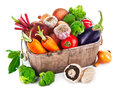 Harvest vegetables in wooden basket on white background Stock Images