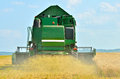 Harvesting the wheat green combine on field at work Royalty Free Stock Images