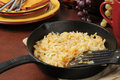 Hash browns in a cast iron skillet golden near serving plates and silverware Stock Photo