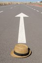 Hat and arrow on an on a asphalt street to the future Royalty Free Stock Image