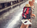 Hat, backpack, map, cellphone and notebook on bench at train station. Royalty Free Stock Photo