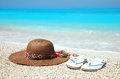 Hat and flip flops on a beach the beautiful Stock Images