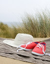 Hat and shoes on beach towel Royalty Free Stock Photo