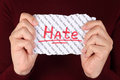 Hate piece of paper with red word in the woman s hands Stock Images