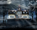 Haunted house with dark scary horror atmosphere around it blue dark sky trees silhouettes and bats coming out of the windows Royalty Free Stock Images
