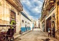 Havana, Cuba - March, 29th 2012: Typical scene of old Havana narrow street and old building, local people and tourists on destroye Royalty Free Stock Photo