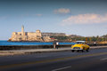 HAVANA - FEBRUARY 17: Classic car and lighthouse in the backgrouClassic old car on streets of Havana, Cuba. Royalty Free Stock Photo