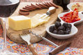 Havarti cheese and savory snacks with red wine including black olives diced bell pepper hummus spicy sausage served a tall elegant Royalty Free Stock Photography