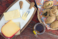 Havarti manchego and gouda cheese served on a cheeseboard with cutters accompanied by red wine a basket of freshly baked Stock Images