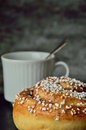 Have a coffee and cinnamon bun moment single cup spoon dark gray background Stock Images