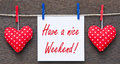 Have a nice weekend text message on white card hung by pegs from washing line with two red spotted hearts hung with red pegs Stock Image