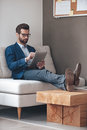 Have some work to do handsome young man keeping legs on table and working with touchpad while sitting on the couch in office Stock Photo