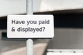 Have you paid and displayed white metal car park sign with black text asking on metal pole manchester uk Stock Image